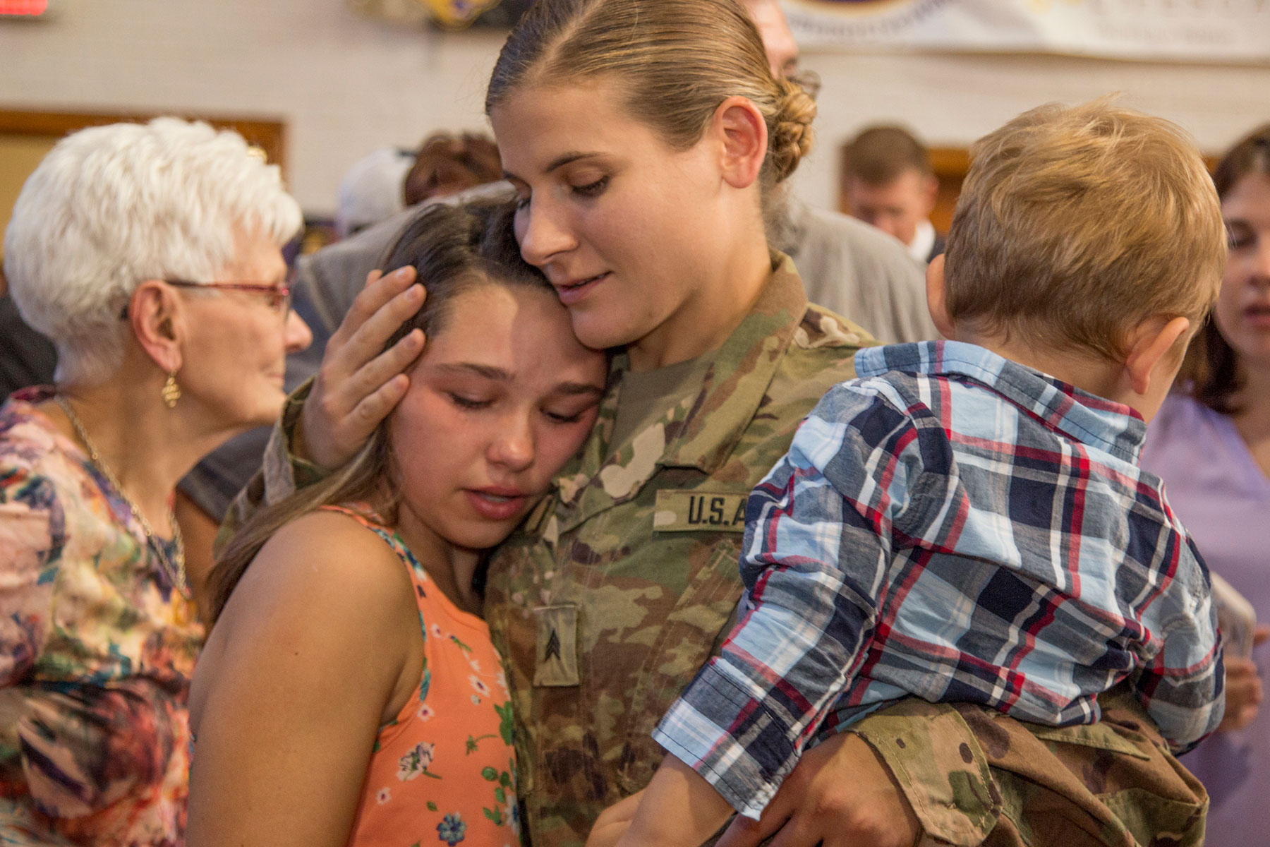 Sgt. Allison Catic, Company A, 248th Aviation Support Battalion, 67th Troop Command, Iowa Army National Guard, embraces her children following the unit's send-off ceremony at Cedar Falls, Iowa, on Sept. 29, 2017. (U.S. Army National Guard/Tawny Schmit)