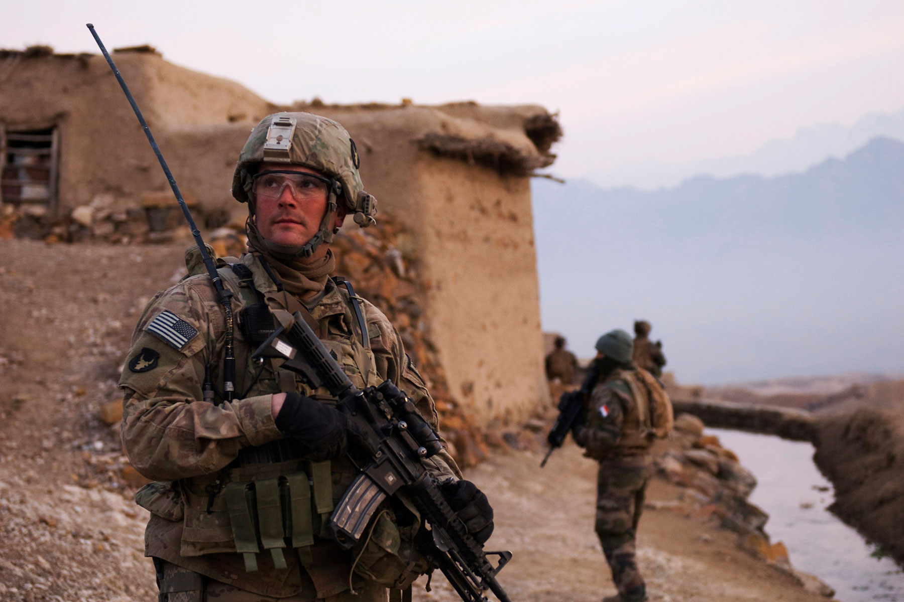 U.S. Army Sgt. Robert Streeter of Newton, Iowa, and a Soldier with Troop B, 1st Squadron, 113th Cavalry Regiment, Task Force Redhorse, scans a nearby hilltop during a search of the Qual-e Jala village. (U.S. Army/Ashlee Lolkus)