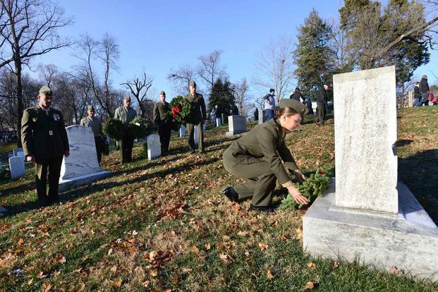 marine decorates grave in arlington cemetery