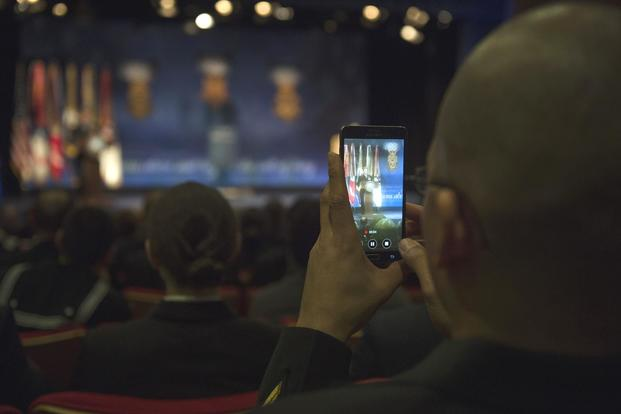 An audience member uses his cell phone to record as MoH recipient Navy Senior Chief Edward Byers provides remarks at the Medal of Honor ceremony honoring his heroism at the Pentagon March 1, 2016. (DoD/Senior Master Sgt. Adrian Cadiz)