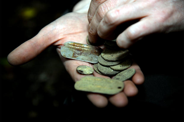 A volunteer displays a pair of dog tags and some coins found near Diss, England, on Sept. 6, 2017. (US Air Force photo/Alexandria Lee)