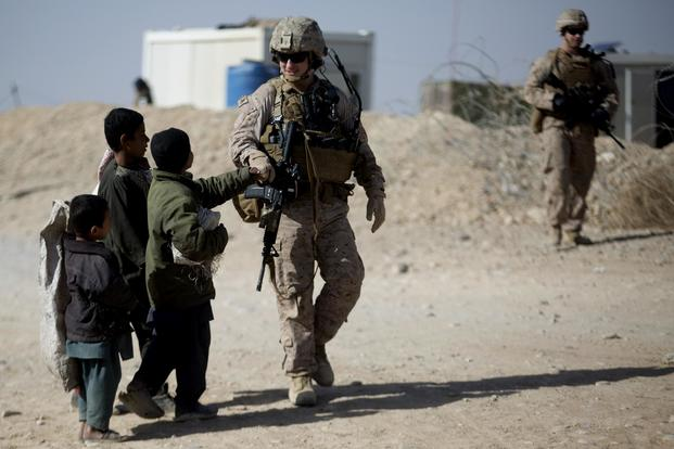A U.S. Marine with Task Force Southwest 18.1 greets local Afghan children during a security patrol near Bost Airfield, Afghanistan, Jan. 16, 2018. (U.S. Marine Corps/Sgt. Sean J. Berry)