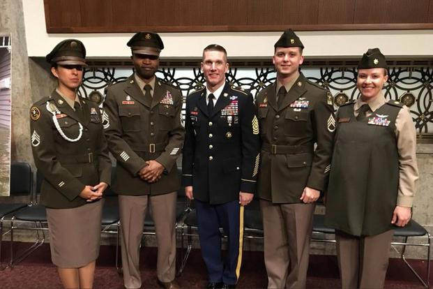 "Four soldiers and Sergeant Major of the Army Dan Dailey display the ""pinks and greens"" uniform prototypes on Capitol Hill, February 1, 2018. (U.S. Army)"