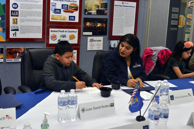 Chrissy Quintero, Army & Air Force Exchange Service inventory specialist, helps third-grader Juan David Rodea give feedback on a meal option under consideration for overseas Department of Defense school. (AAFES)