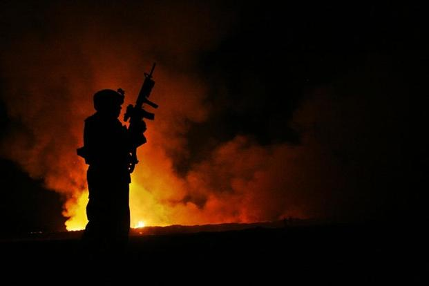 A Marine watches over a burn pit at Camp Fallujah, Iraq, May 25, 2007. (Samuel Corum/U.S. Marine Corps)
