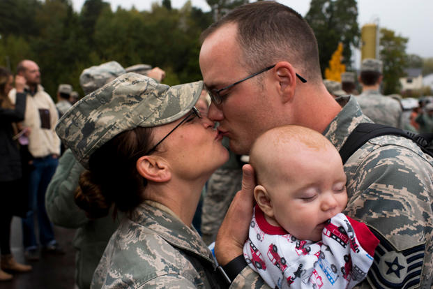 Two Airmen assigned to the 606th Air Control Squadron kiss while holding their infant son, born during the father's deployment. (U.S. Air Force/Joe W. McFadden)