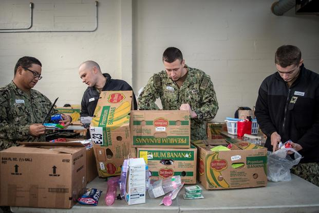 Sailors assigned to the Los Angeles-class fast-attack submarine USS Olympia (SSN 717) sort through donated food items for the Thurston County Food Bank in downtown Olympia, Wash., March 17. (U.S. Navy/Mass Communication Specialist 2nd Class Nancy C. diBenedetto)