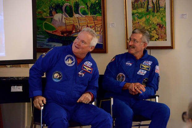 Retired Capt. Dan Burbank and retired Cmdr. Bruce Melnick, speak about their careers as NASA astronauts and Coast Guard aviators at an event sponsored by the Coast Guard Heritage Museum, Saturday, May 19, 2018, in Barnstable, Massachusetts. They are the only two people in history to have been both astronauts and Coast Guard members. (U.S. Coast Guard photo/Lara Davis)
