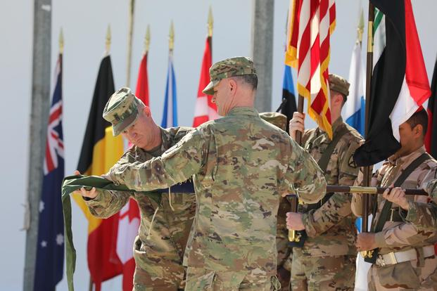 Maj. Gen. Walter Piatt, right, commander of Combined Joint Forces Land Component Command and his senior enlisted advisor, Command Sgt. Maj. Samuel Roark, left, rolls up the CJFLCC flag during a deactivation ceremony in Baghdad, Iraq, April 30, 2018. (U.S. Army/Sgt. Jonathan Pietrantoni)