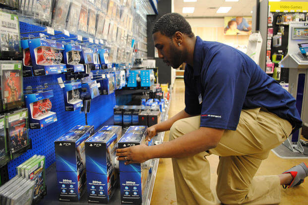 AAFES employee Travis Daniels organizes video game consoles in the electronics department at The Exchange on Grand Forks Air Force Base, North Dakota. (U.S. Air Force/Luis Loza Gutierrez)