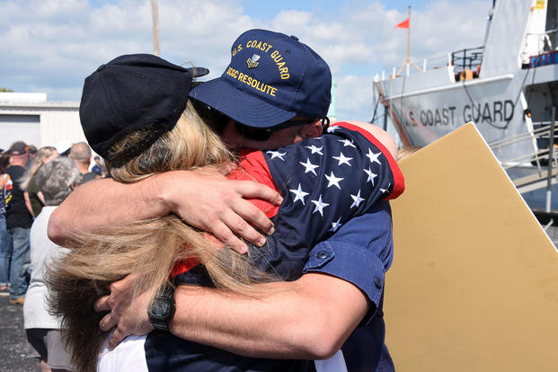 Petty Officer 1st Class Evan Means, a crewmember aboard the Coast Guard Cutter Resolute, hugs a family member after returning home to St. Petersburg, Florida (U.S. Coast Guard/Ashley J. Johnson)