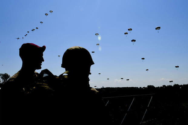 Paratroopers look on as others fall from the sky June 3 near Sainte-Mere-Eglise, France, during the D-Day 74 commemorative airborne operation.