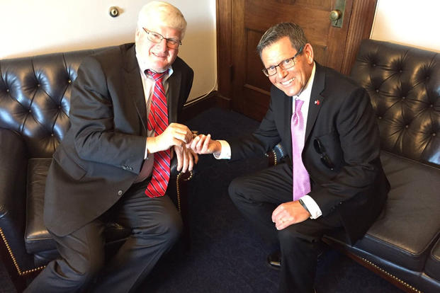 U.S. Congressman Glenn Grothman (left) discusses veterans issues with Jake Leinenkugel (right) as he presents Grothman with a Veterans Day pin. (Photo: Rep. Glenn Grothman, grothman.house.gov)