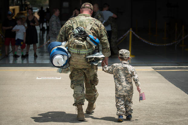 A boy reunites with his father during a homecoming ceremony at the Kentucky Air National Guard Base in Louisville, Kentucky. (U.S. Air National Guard/Dale Greer)