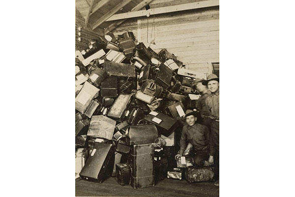 Soldiers finished with stateside training pose next to the large pile of luggage destined for their homes as they ship overseas. (Photo: National Archives and Records Administration)