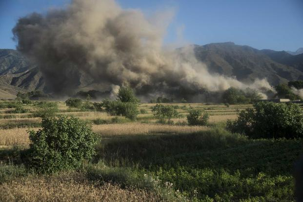 In coordination with U.S. Special Forces, Afghan Commandos call in an airstrike on a target building found to be rigged with improvised explosive devices in support of a SOTF-A clearance operation in Nangarhar province Afghanistan, on June 12, 2018. (NATO photo by U.S. Air Force Master Sgt. Michael Garza)