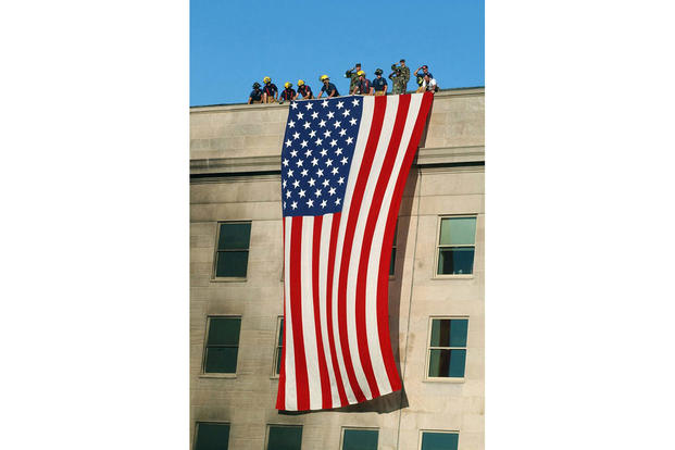 Soldiers from the 3rd Infantry Regiment (The Old Guard) render honors as firefighters and rescue workers unfurl a huge American flag over the side of the Pentagon while rescue and recovery efforts continued following the Sept. 11, 2001, terrorist attack. The garrison flag, sent from the U.S. Army Band at nearby Fort Myer, Virginia, is the largest authorized flag for the military. (Navy photo by Petty Officer 1st Class Michael Pendergrass)