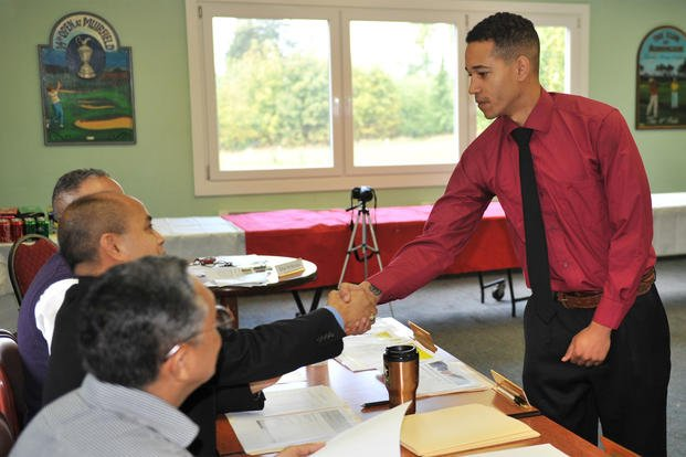 Spc. Joshua Walton, a soldier assigned to the Warrior Transition Battalion-Europe, greets interview panel members during his mock interview Sept 18, at Baumholder's Rolling Hills Golf Club. (Photo Credit: Gino Mattorano)
