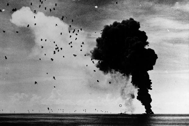 USS Abner Read (DD 526) afire and sinking in Leyte Gulf, November 1, 1944, after being hit by a kamikaze. A second Japanese suicide plane (circled) is attempting to crash another ship; however, this one was shot down short of its target. (U.S. Navy photo)