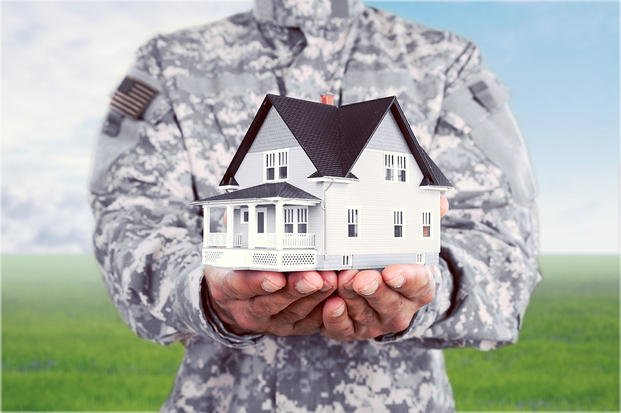 Servicemember in uniform holding house in hands