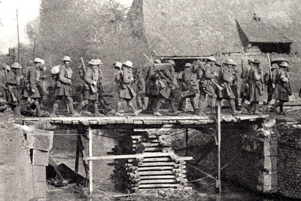 New York National Guard soldiers of the 27th Infantry Division cross a bridge over the LeSelle River on their way to St. Souplet, France during the Hindenburg Line campaign in the fall of 1918. The bridge was built by the Soldiers of the 102nd Engineer Battalion. (New York State Military Museum photo)