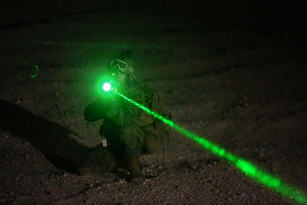 A student with Infantry Officers Course 4-14, provides security for the extraction of American non-combatant role players after the long-range vertical insertion of a Company Landing Team during Exercise Talon Reach IV at Range 220, Sept. 19, 2014. The prospective infantry officers pointed a non-lethal laser at simulated protesters, which can cause nausea and disorientation. (U.S. Marine Corps photo/Lauren A. Kurkimilis)