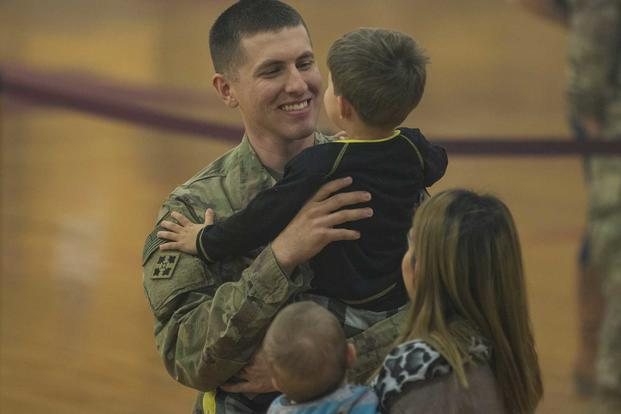 A soldier, assigned to 2nd Infantry Brigade Combat Team, 4th Infantry Division, returning from an overseas deployment, holds his son following a homecoming ceremony Oct. 31, 2018, held at the William Bill Reed Special Events Center at Fort Carson, Colorado. A different type of veteran is emerging from the post-9/11 wars that will force veterans organizations to adapt. (U.S. Army photo by Spc. Robert Vicens)