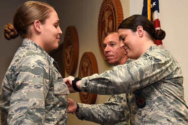 U.S. Air Force Lt. Col. Scott Cline, 312th Training Squadron commander, watches as Airman 1st Class Erin Prosser pins a duty badge onto Airman Emma Prosser at her graduation from the Louis F. Garland Department of Defense Fire Academy on Goodfellow Air Force Base, Texas, Dec. 3, 2018. Erin and Emma Prosser are twins, Erin joined the Air Force shortly before her sister and graduated the fire academy in March of 2018. (U.S. Air Force photo/Seraiah Hines)