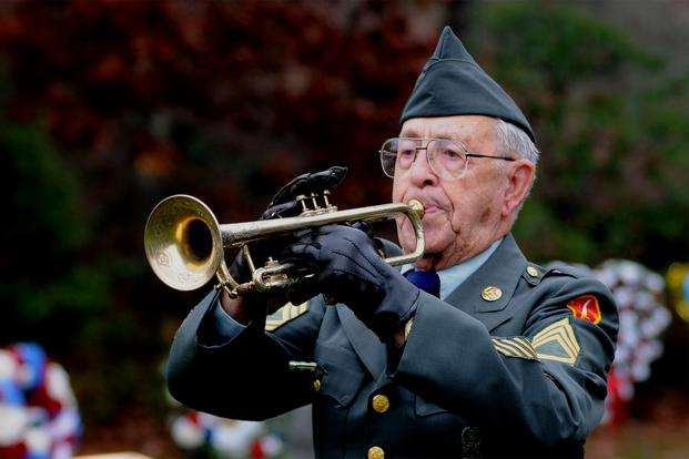 "Nov. 7, 2010: Albert J. Madden plays ""Taps"" on his trumpet during a ceremony marking Veterans Day at Massachusetts National Cemetery. (US Air Force photo)"