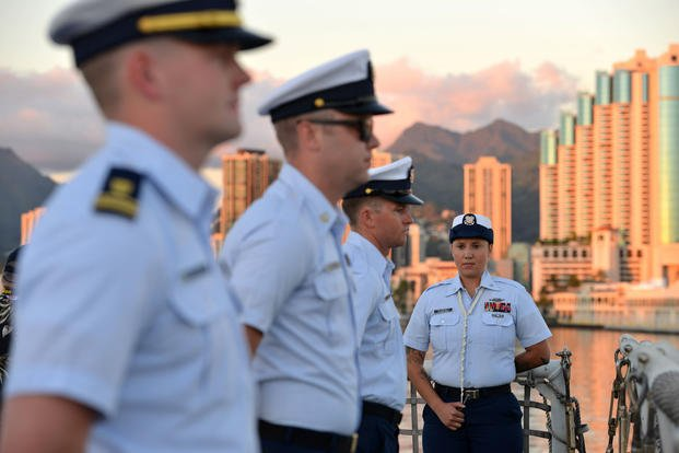 Coast Guard Cutter Sherman crewmembers line the rail of the flight deck prior to evening colors during a ceremony aboard the Sherman in Honolulu, Mar. 28, 2018. (U.S. Coast Guard photo/Matthew Masaschi)