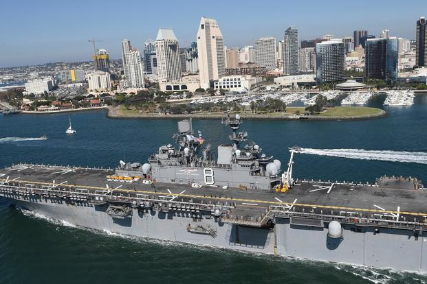 Sailors and Marines stationed and embarked aboard USS Makin Island (LHD 8) man the rails of the amphibious assault ship as they pass by downtown San Diego to begin their scheduled 7-month deployment. (U.S. Navy/Petty Officer 1st Class Jason J. Perry)