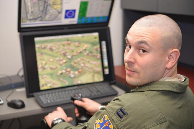 "Capt. Andrew Byrd, 451st Flying Training Squadron combat systems operator flight commander, demonstrates use of a ""T-28"" computer simulator. Byrd designed the simulator to enhance technical training, allowing student CSOs to experience their role while orbiting a target area in support of realistic-looking friendly troops who can be seen on a monitor. (Photo by Randy Martin)"