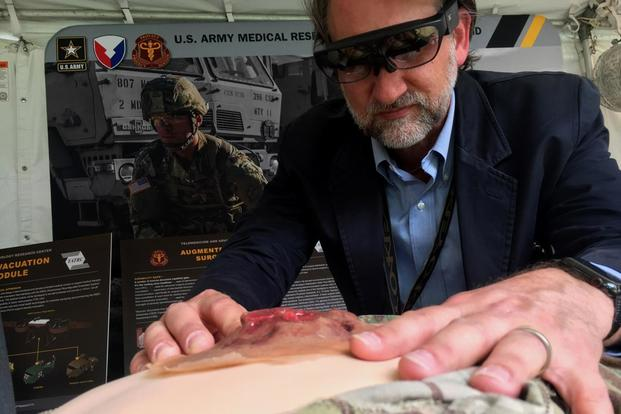 Geoffrey Miller, a research scientist at the Army's Medical Research and Materiel Command, shows how medics may one day us a heads-up display that can connect them to a surgeon in a hospital for help when treating personnel on the battlefield. (Matthew Cox/Military.com)