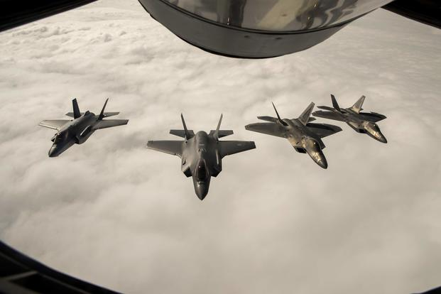 Two F-22 Raptors from the 95th Fighter Squadron, 325th Fighter Wing, based at Tyndall Air Force Base, Fla., fly in formation and conduct training operations with two Royal Norwegian air force F-35A Lightning II aircraft during an air refueling over Norway on Aug. 15, 2018. (U.S. Air Force photo by Senior Airman Preston Cherry)