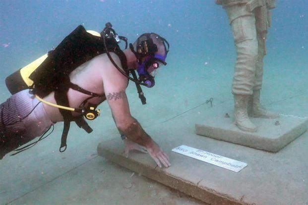 Shawn Campbell, a former staff sergeant and now a master diver, looks at his name on a plaque next to one of the statues at the Circle of Heroes underwater veterans memorial off the coast of Clearwater, Fla. (U.S. Army/Video still by Bill Mills)