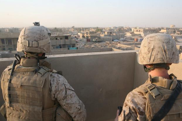 Petty Officer 3rd Class Benjamin Swain, front, a corpsman with 3rd Battalion, 11th Marine Regiment, Regimental Combat Team 1, and Maj. Jeffrey McCormack, the operations officer for 1st Battalion, 9th Marines, glance over the city of Fallujah from the roof a building, Sept. 17, 2008. The roof of the building was the last place McCormack saw James, Benjamin's brother, alive. (Casey Jones/U.S. Marine Corps)
