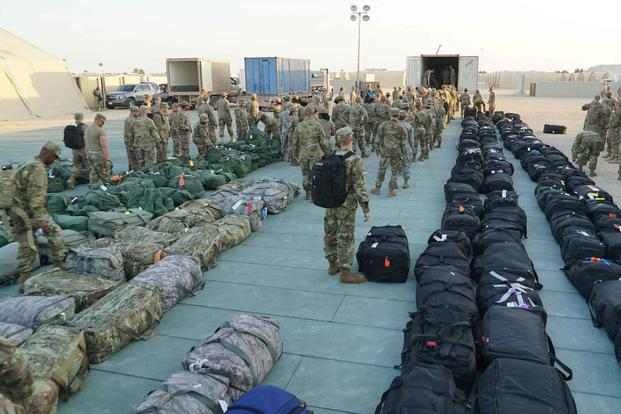 U.S. airmen finish unloading a baggage truck and begin the process of finding their bags at Prince Sultan Air Base (PSAB), Saudi Arabia, on Nov. 26, 2019. The U.S. is partnering with the Kingdom of Saudi Arabia at PSAB to enhance operational flexibility while maintaining security and stability in the region. (U.S. Air Force photo by Senior Airman Matthew Zakrzewski)