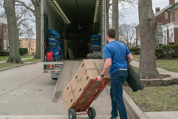 A moving contractor loads a truck with a service member's goods during the PCS peak-season at Scott Air Force Base,.