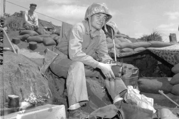 Marine Sgt. Arthur J. Kiely Jr. sits on in a position on Pacific island during World War II, wearing the 1911 Colt .45 automatic pistol.