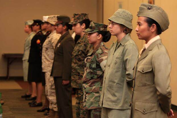 Marines display the different uniforms women have worn since World War I during the Women's History Month fashion show.