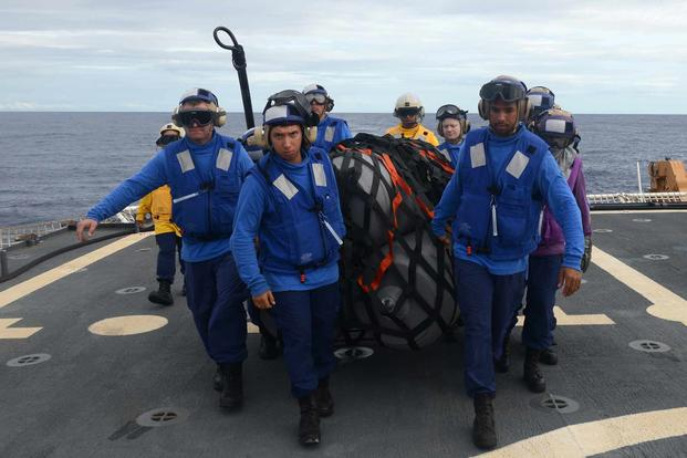 The crew of the Coast Guard Cutter Kimball moves simulated supplies.