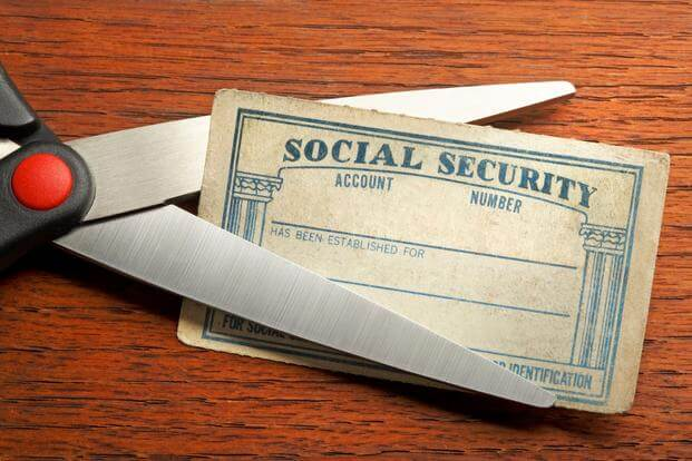 Image of social security card being cut in half, symbolizing a social security tax cut