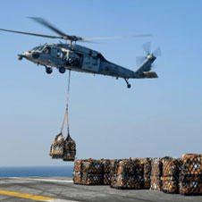helicopter lifting cargo from aircraft carrier