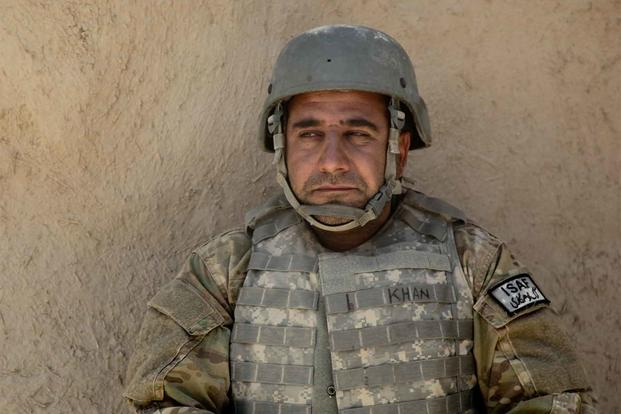 An interpreter rests near a wall in Afghanistan.