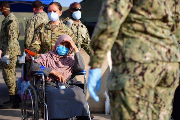Senior Airman Romero assists an Afghan evacuee.