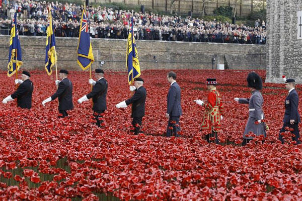 Crowds watch a remembrance day ceremony at the ceramic poppy art installation by artist Paul Cummins entitled 'Blood Swept Lands and Seas of Red' in the dry moat of the Tower of London in London, Tuesday, Nov. 11, 2014. (AP Photo/Kirsty Wigglesworth)