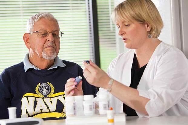 Navy veteran in consultation with his nurse. (Photo: Department of Veterans Affairs)