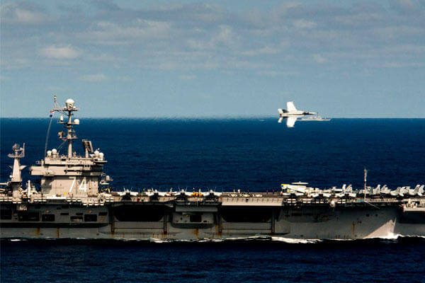 An F/A-18E Super Hornet performs a flyby over the aircraft carrier USS John C. Stennis (CVN 74). Defense Secretary Ashton Carter visited the carrier during a trip to the South China Sea. (US Navy/Tomas Compian)