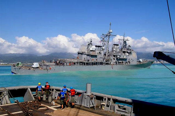 Civil service mariners, on board the Military Sealift Command rescue and salvage ship USNS Salvor, work to debeach the grounded USS Port Royal in February 2009. (US Navy photo)