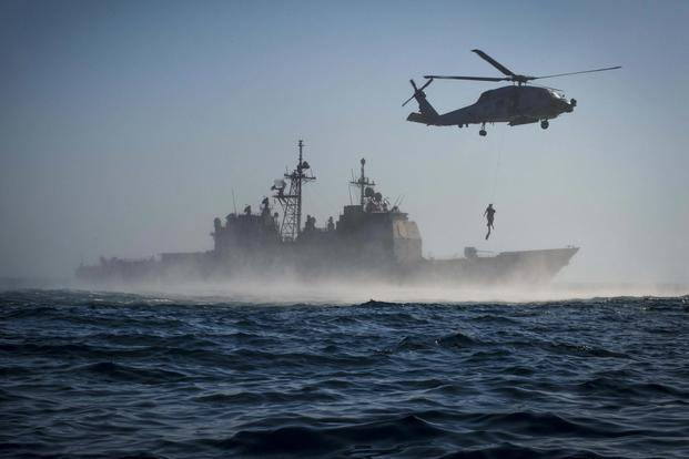 The guided-missile cruiser USS Monterey and an MH-60R Sea Hawk helicopter assigned to Helicopter Maritime Strike Squadron Forty-Eight conduct search and rescue training evolution on Sept. 23, 2016. Petty Officer 2nd Class William Jenkins/Navy